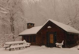 A cabin, in the woods, by the river, on a snowy morning. The warmth inside from the fireplace. Life is quiet, and good.
