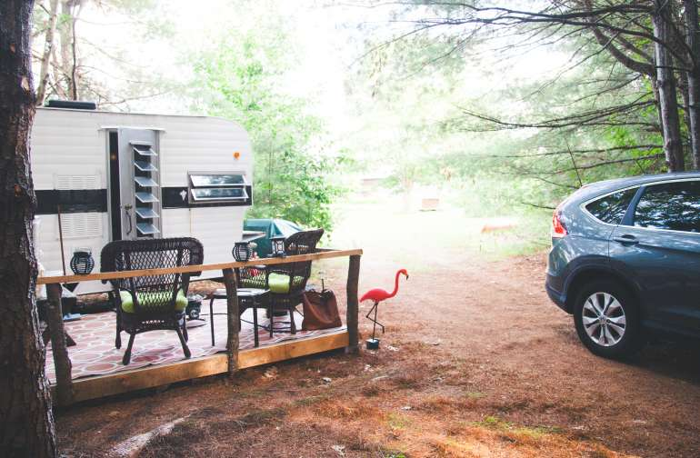 The outside of the camper- complete with a deck, picnic table, gas fire pit, and chairs.