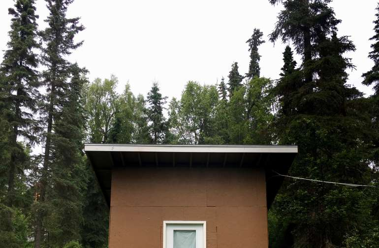 The cabin is surrounded by towering spruce trees on 3 sides