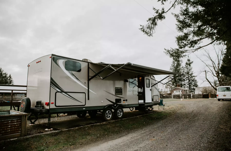Take a break from the sun with the built in awning, late model RV includes outdoor kitchen, 2 bunk beds, 1 queen, fold out sofa bed and convertible kitchen table bed.