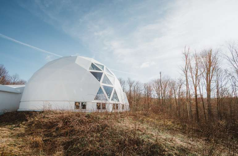 This geodesic dome with a passive solar design serves as the future home of a kitchen and bathroom. It's the community gathering space.