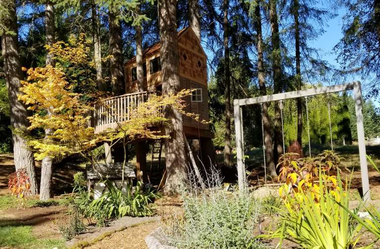 The tree house is surrounded by gardens and a swing set