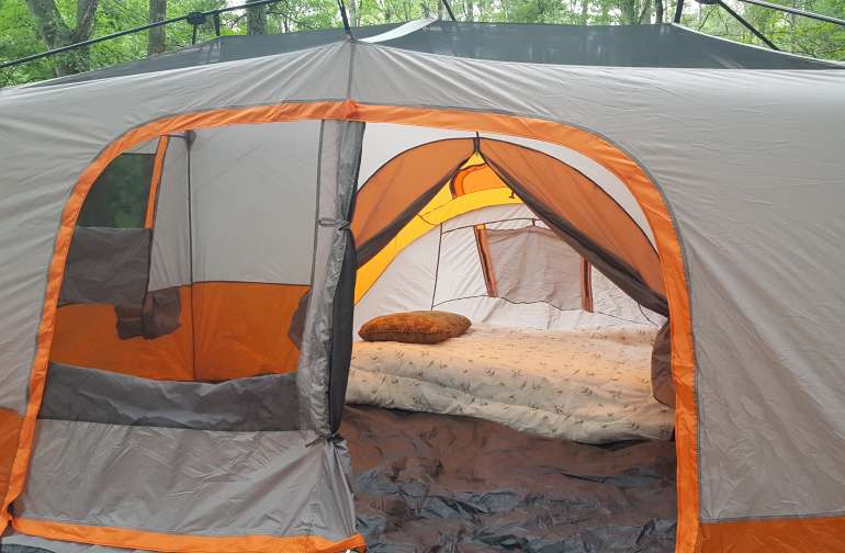 The tent is provided.  This is a large 14 x 10 foot tent. Queen size air mattress is provided .  You bring your own linens
