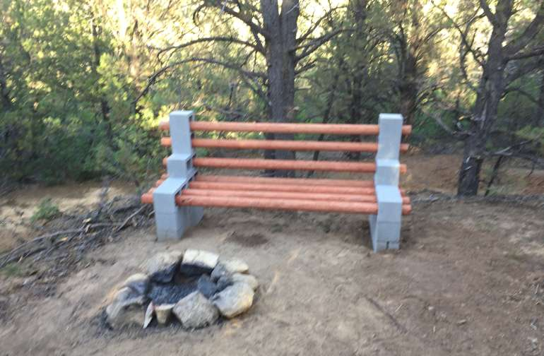 Campfire and bench. You can see the tent pad just down the hill behind the bench.