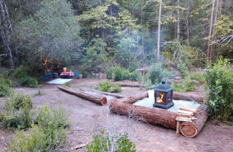 large fire pit area with a covered easy up, tables, water, and a propane stove