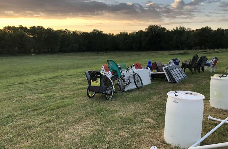 Cow pasture in the distance. Our bike and trailer leaning against their festival supplies.