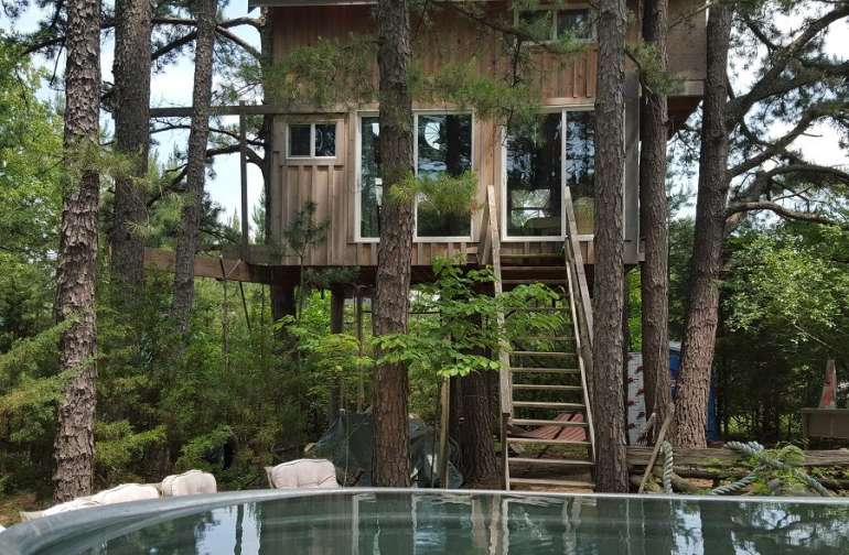 Our Enchanted 2 Story Treehouse is set in a beautiful pine forest. In the foreground you see our Old Time Tin Hot Tub.