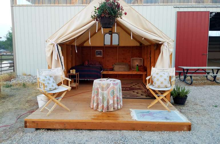 Our glamorous camping tent is cowgirl chic and fun! A custom-made wall tent is placed on a wooden platform with real wooden walls. Two single, comfy beds have linens and warm blankets. The whole tent is furnished with rustic ranch ambiance.