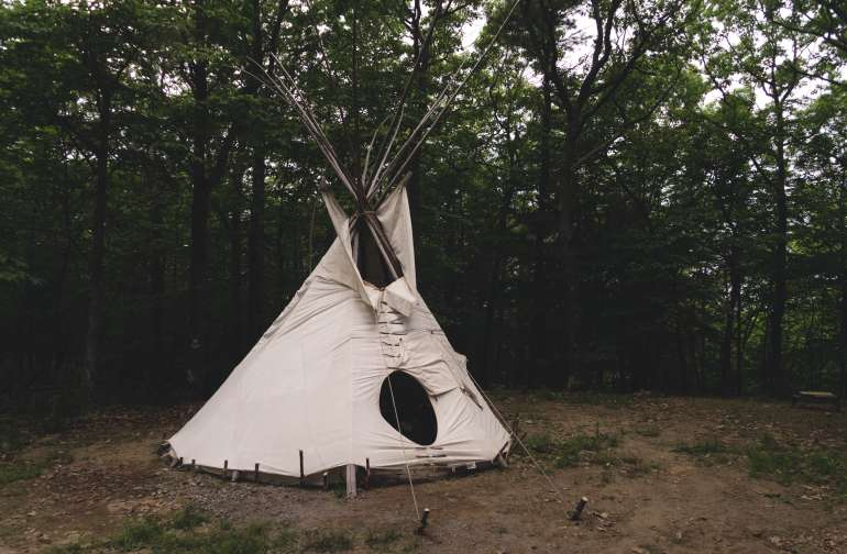 The brand-new teepee from the outside. There's a hammock outside and it's located in a clearing with plenty of room to live.