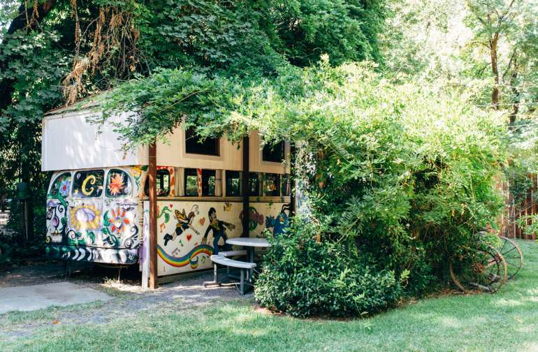 The bus is covered by a lush arbor