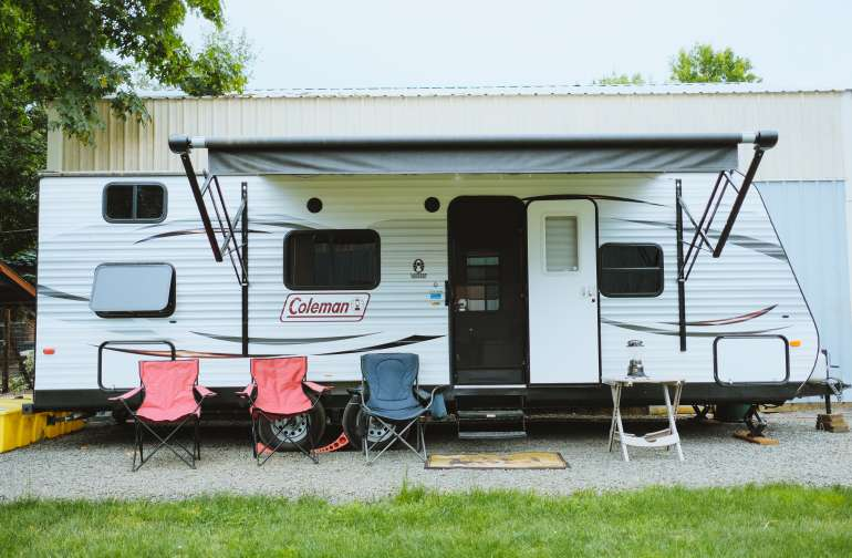 The exterior of the camper. Complete with chairs for friends and an awning to enjoy any kind of weather.