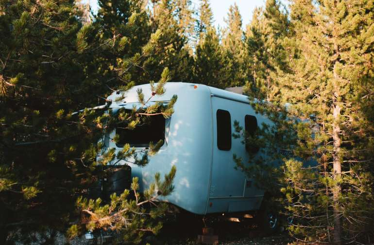 the camper is tucked away in the woods, surrounding by trees