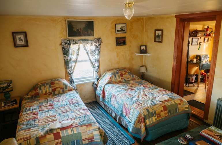 Two twin beds in the main room of Cow Camp