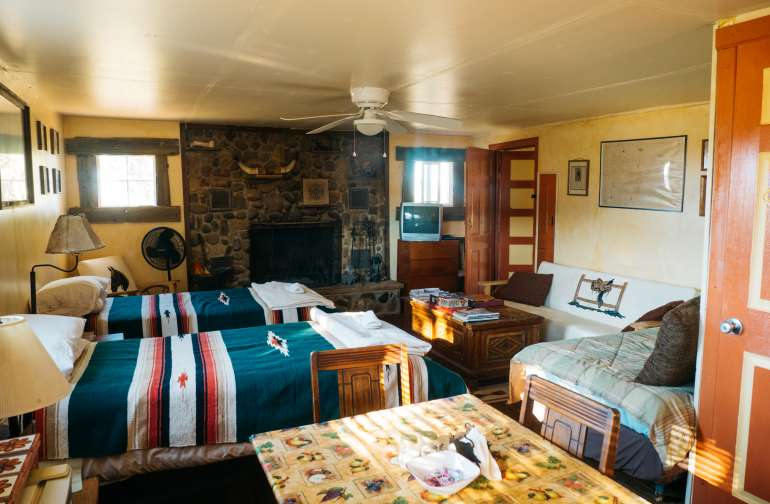 Delightful main room, including three twin beds, full kitchen, fireplace, and couch great for reading and testing out their board games.