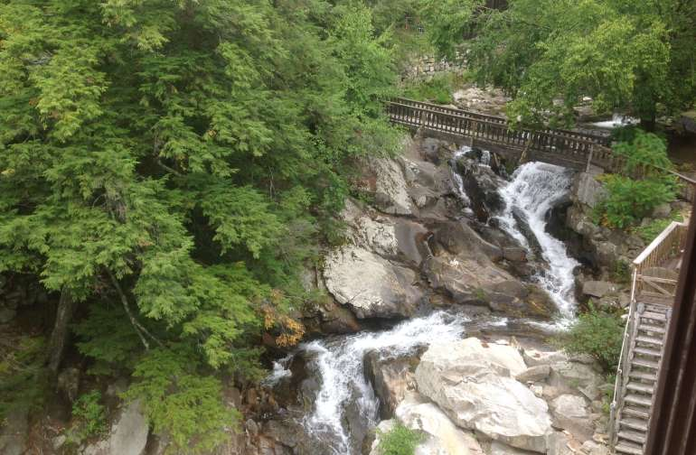 Looking upstream from the Millhouse at the footbridge and upper falls. Campsite is just to the right.