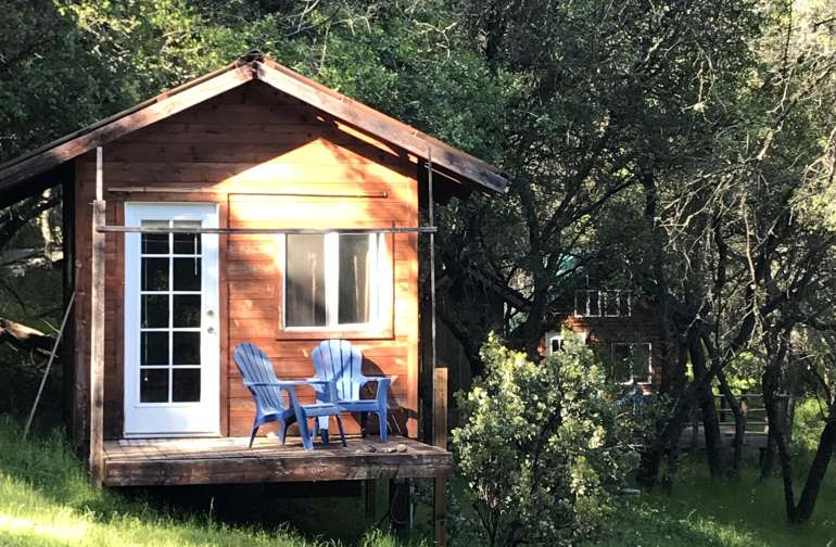 Cabin no. 1 at Oaks and Stream. Contains a double bed, dresser, chair, and heater.