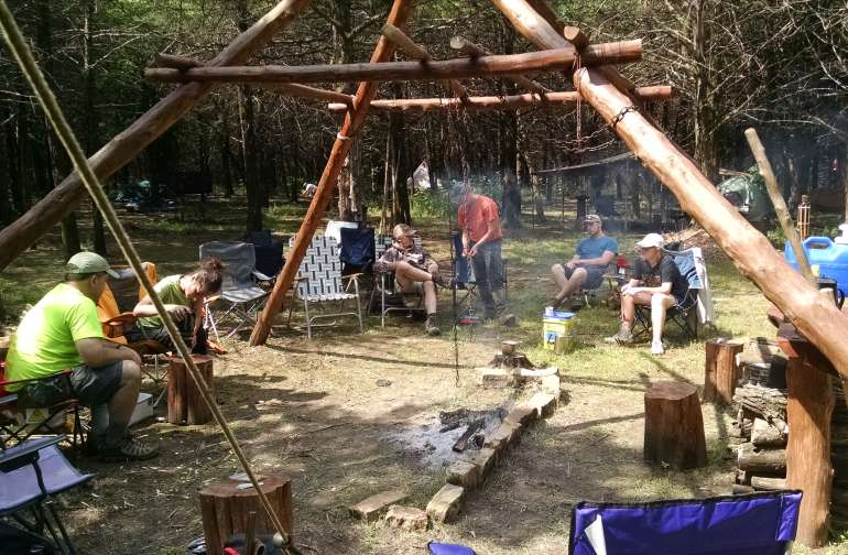 Campers relaxing around the central cooking structure.