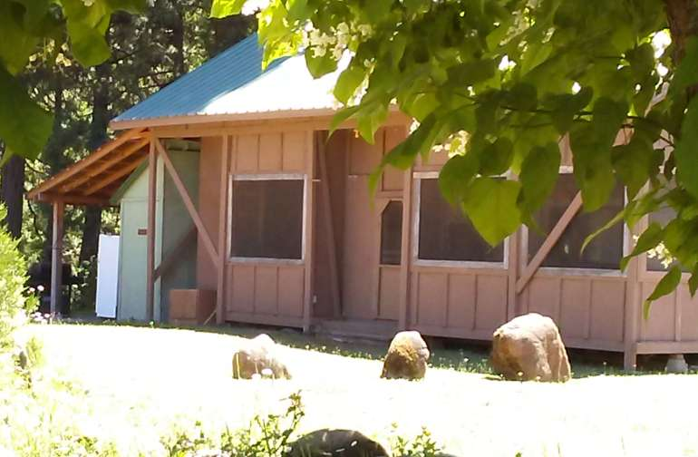 Screen porch with 28' trailer inside for Glamping.  Communal kitchen, bath, picnic area in the back.