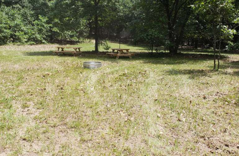 Picnic tables and firepit provided at campsite.