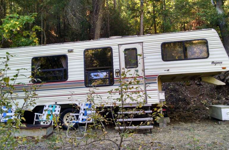 Vintage camper off-grid in the forest. It will sleep four comfortably with two double beds and a table that converts too. As a bonus it has some water for bathing and clean up, propane refrigerator, stove and oven, and some electricity for lights too.