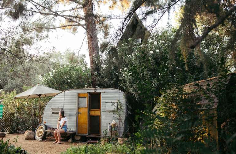 The trailer is nestled between an abundance of greenery and the A-Frame cabin.