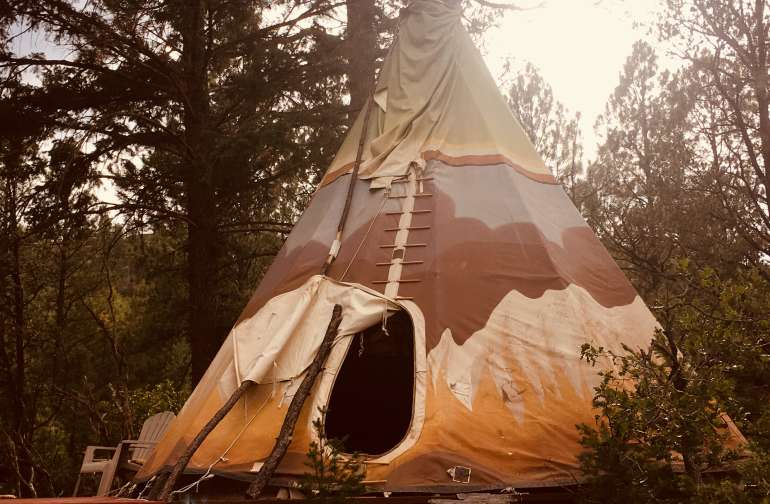 """Hand painted 18' """"Prairie Fire"""" tipi on deck."""