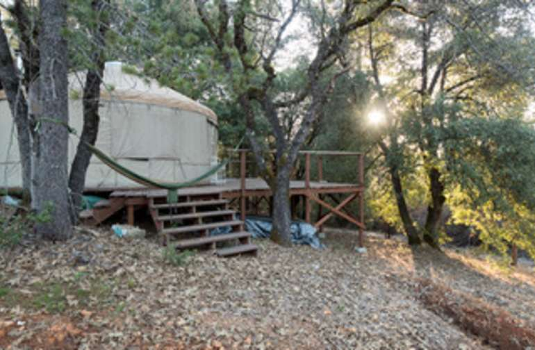 This view of the yurt shows the deck and hammock lounge zone. The window flaps are rolled down in the picture but are open most of the year.